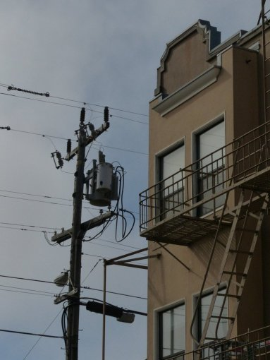 Lines of telephone pole and fire escape, side-by-side.